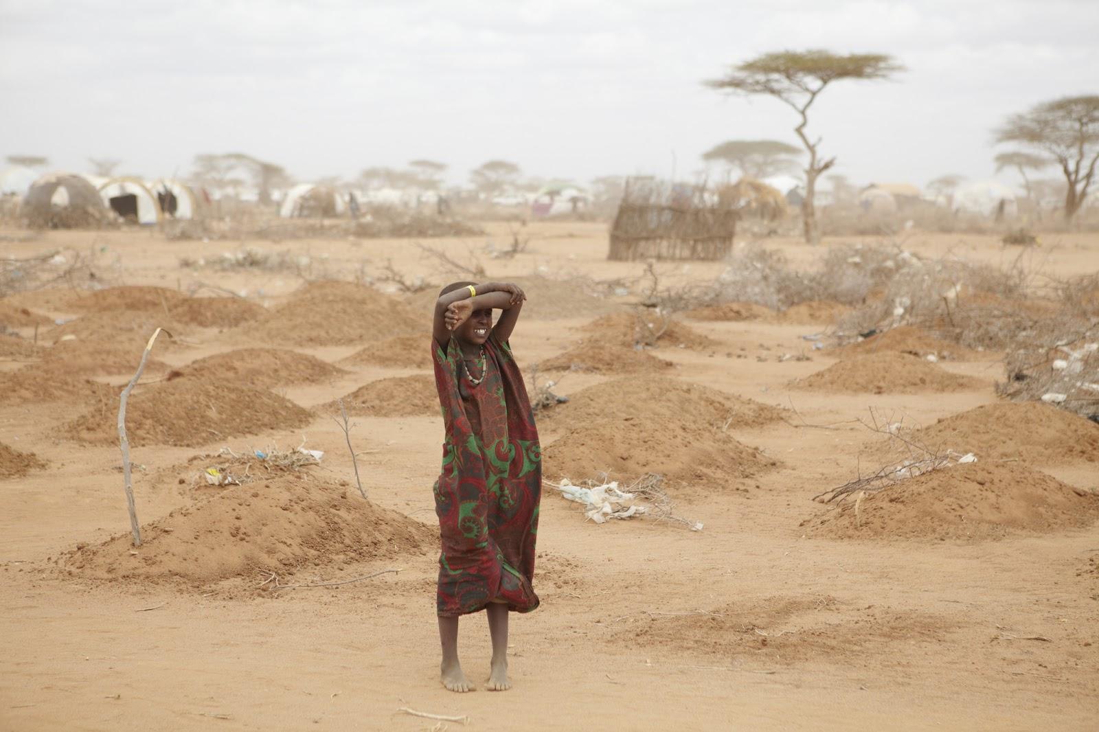 Une jeune fille au milieu des tombes de 70 enfants, pour la plupart morts de malnutrition dans le camp de réfugiés de Dabaab. Crédit : Wikimédia.